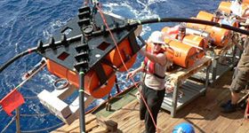 Seismographic equipment is lowered into the sea.